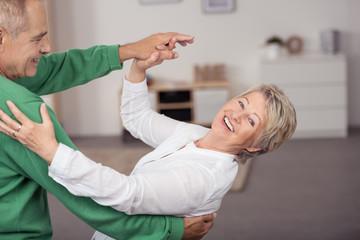 lachende senioren tanzen durch ihre wohnung