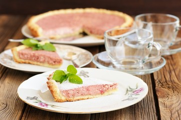 Strawberry tart with two cut pieces decorated with fresh mint an