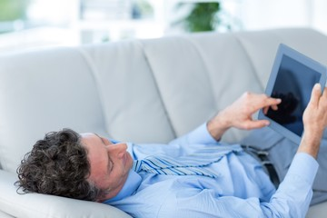 Businessman using his tablet on couch
