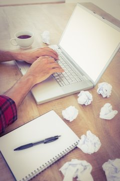 Hands typing on a laptop with paper pellets beside