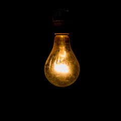 Old light bulb glowing in dark.