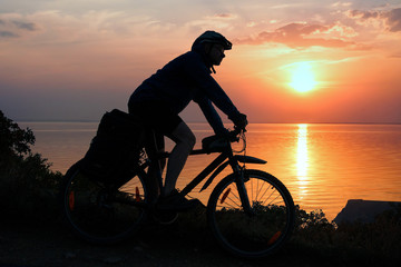 Silhouette of a cyclist in the rays of the setting sun