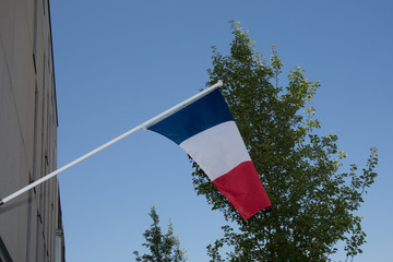 A French flag waving over a blue sky