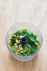Ingredients for Pesto Sauce with Pistachio Nuts in a Plastic Bowl of Food Processor on Rustic Wooden Background