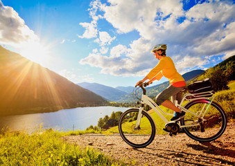 woman with e-bike above a lake in sunset/e-power 11