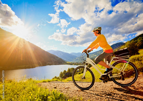 woman with e bike above a lake in sunset e power 11. Black Bedroom Furniture Sets. Home Design Ideas