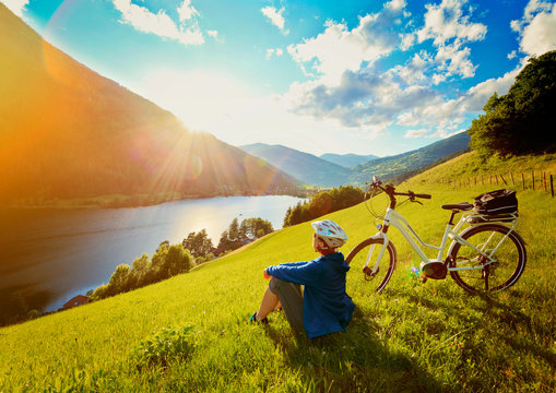woman resting above a lake with her e-bike/e-power 14