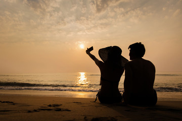 Couple using a smartphone camera itself is Selfie beach during s