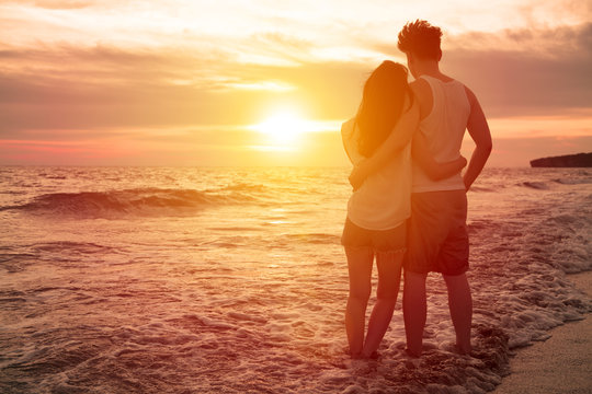 young couple watching sunset on the beach