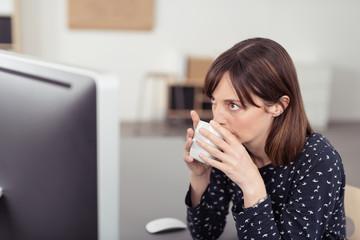 frau trinkt kaffee im büro und schaut auf computer