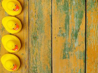 Rubber ducks on wood