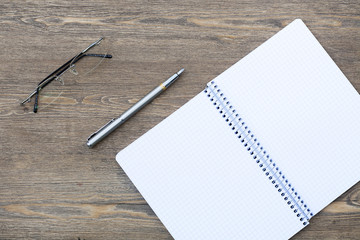 Expand spiral notebook into a cell with a pen, pencil, eraser and glasses on a wooden table, selective focus