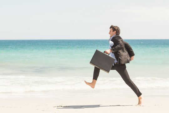 Businessman jumping in front of the sea