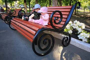 small children sit on a park bench