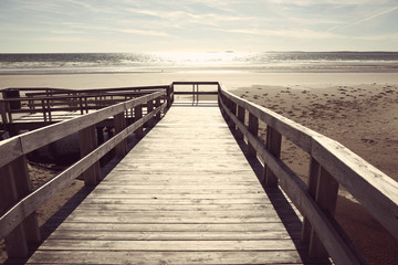 boardwalk to sandy beach and ocean with instagram filter effect