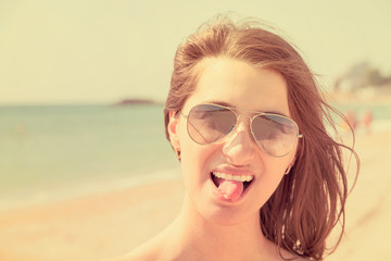Retro Effect Of Portrait Happy Young Woman Portrait Sticking Out Tongue On Beach