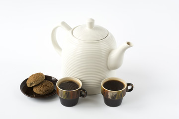 Two ceramic cups of coffee with cookies on a dish and a ceramic