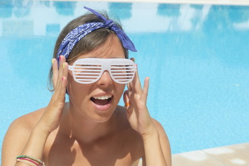 Girl with crazy sunglasses posing by the pool