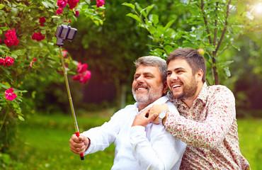 like father like son. family makes selfie on smartphone