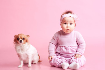Baby girl sitting on floor with little dog over pink. Wearing stylish clothes. Looking at camera. Childhood.