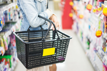 Woman with shopping basket in supermarket.