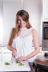junge Frau schneidet Basilikum in der Küche