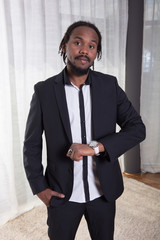junger Afrikaner im Anzug schaut auf die Uhr