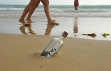 Botella con el símbolo del euro en la playa entre la gente caminando por la orilla