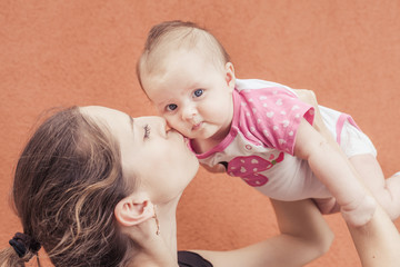 Happy mother kissing her baby at wall background. Baby looking at camera. Mothercare is most important in baby life. Image ready for International Kissing Day or World Kiss Day