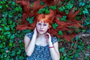 beautiful redhead girl lying in ivy