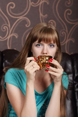 Young beautiful woman drinks coffee from gilt cup on couch