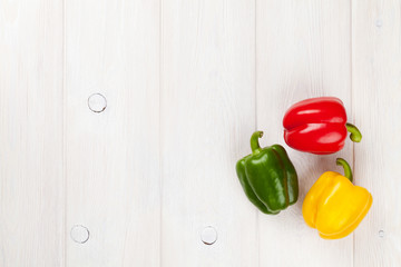 Colorful bell peppers on white wooden table