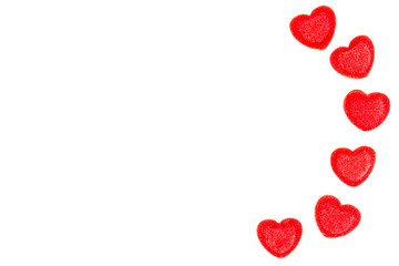 Red heart-shaped sugar sprinkles on white background