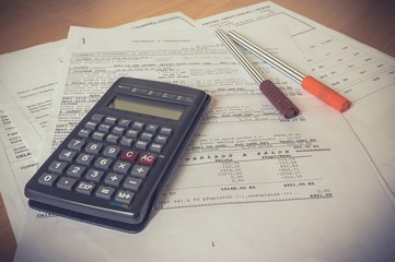 Business composition of bills, calculator, pen and various statistics on the table