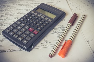 Calculator and pens on bank statement on the table