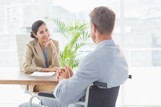 Smiling businesswoman interviewing disabled candidate
