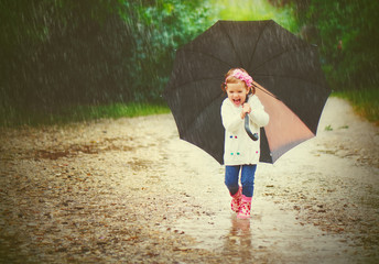 happy baby girl with an umbrella in the rain runs through