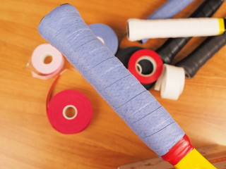 Freshly wrapped blue over grip on a Tennis racket providing a tacky surface for a firm grip, with grip work materials in the background