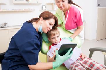 Modern dental team entertaining kid or child patient