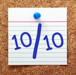 A perfect score or grade of ten out of ten in blue text on an index card pinned to a cork notice board