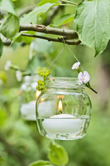 Kerze im Glass hängt im Baum