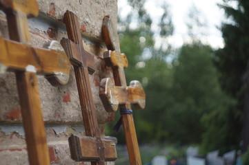 Three Orthodox crosses leaning against the brick wall.