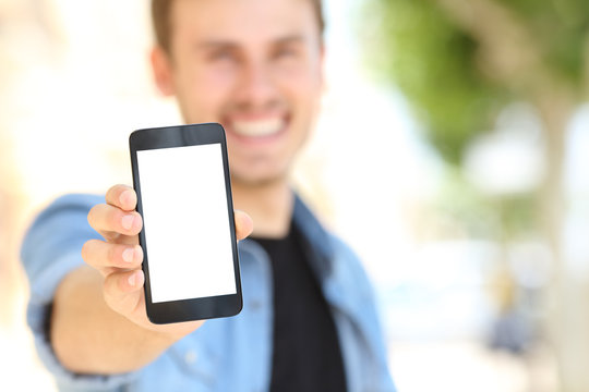 Man showing a blank phone screen in the street