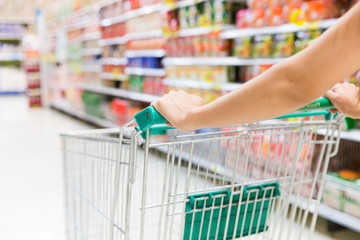 Women with shopping cart in supermarket store.