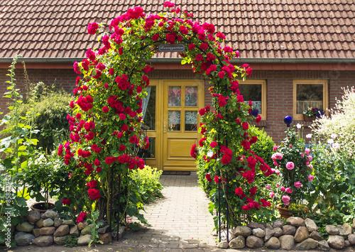 romantischer vorgarten mit rosenbogen stockfotos und