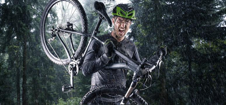 Nasser Mountainbiker mit Fahrrad auf der schulter