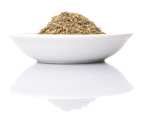 Dried thyme herbs in white bowl over white background