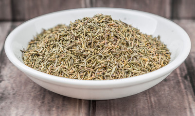 Dried thyme herbs in white bowl over weathered wooden background