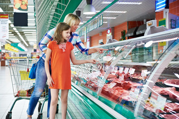 Mother and daughter chooses a meat in shop