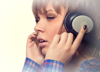 Beautiful young woman listening to music on headphones.